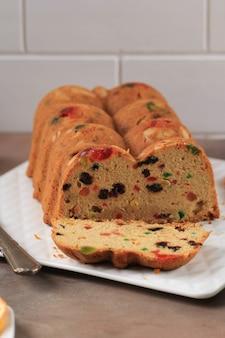Tranche de délicieux pouding au gâteau aux fruits anglais fait maison avec des fruits mélangés séchés, des raisins secs, des raisins secs et des amandes hachées. servi pendant la fête de noël ou le réveillon du nouvel an