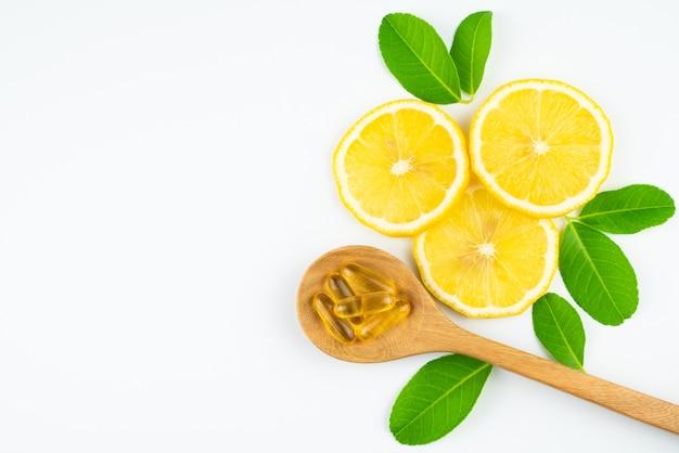 Tranche fraîche de citron avec des feuilles, supplément de capsule de vitamine c de naturel isolé sur fond blanc