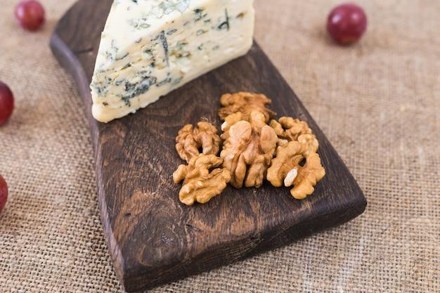 Tranche de fromage bleu avec des noix et des raisins sur un mur rustique.