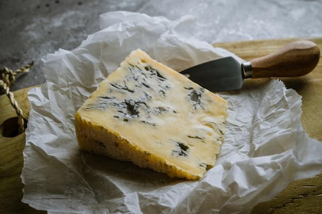 Tranche de fromage bleu sur planche de bois avec couteau à fromage