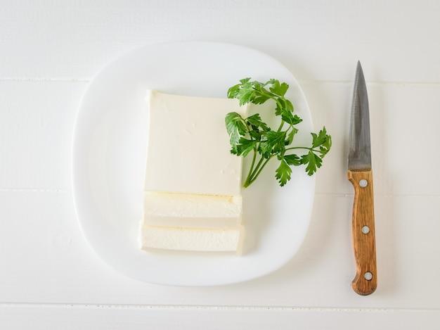 Tranche de fromage serbe tranché avec du persil sur une assiette posée sur une table blanche.