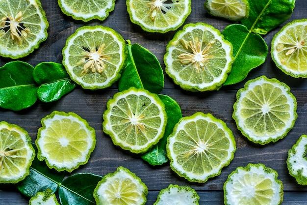 Tranche de fruits de bergamote et de feuilles sur la vieille table en bois