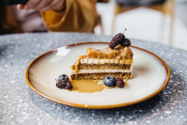 Une tranche de gâteau au café au caramel garnie de sauce au caramel, de myrtille et de framboise dans une assiette sur une table en granit.