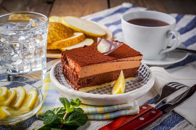 Une tranche de gâteau au chocolat sur une assiette, une tasse de thé, citron, eau glacée, des tranches de poire.