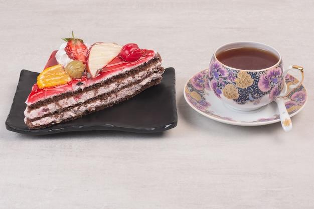 Tranche de gâteau au chocolat sur une assiette avec des tranches de fruits et une tasse de thé.