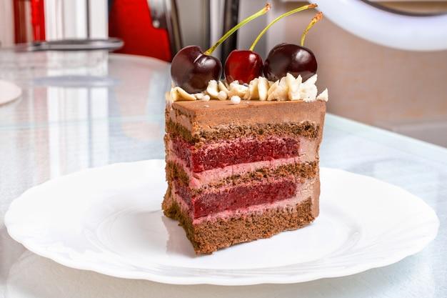 Tranche de gâteau au chocolat au caramel avec des cerises sur une plaque blanche