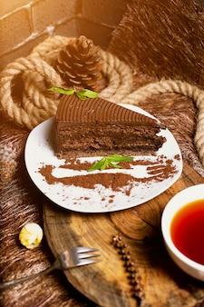 Tranche de gâteau au chocolat et cacao servie avec des feuilles de menthe