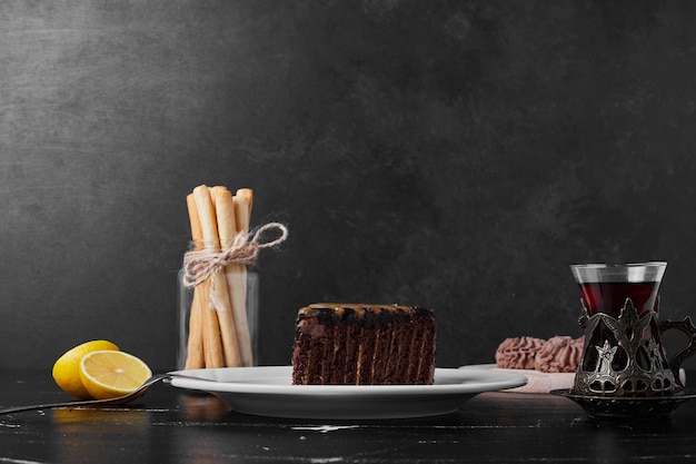 Une tranche de gâteau au chocolat dans une assiette blanche avec un verre de thé.