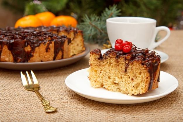 Tranche de gâteau au chocolat décorée de bouquet de viorne, tasse de café, oranges sur table avec branche d'épinette et sac.