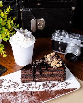 Une tranche de gâteau au chocolat garnie de glaçage au chocolat et d'amandes