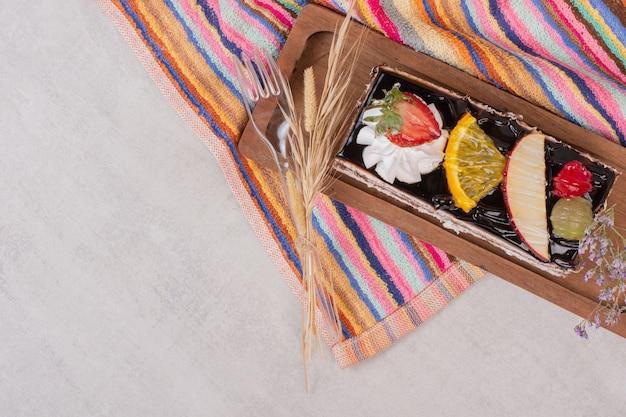 Tranche de gâteau au chocolat sur planche de bois avec des tranches de fruits.