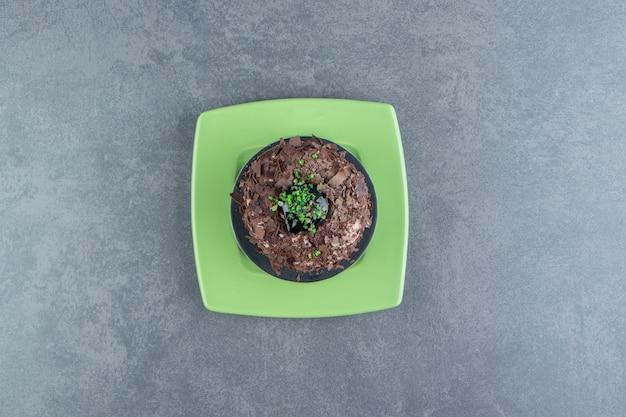 Tranche de gâteau au chocolat sur plaque verte.