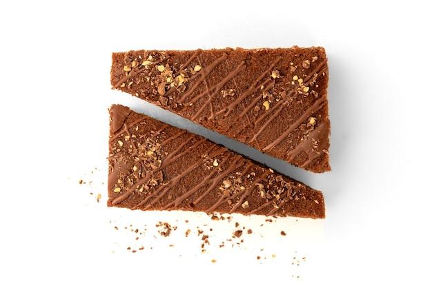 Tranche de gâteau au chocolat avec remplissage de lait et chocolat isolé sur blanc.