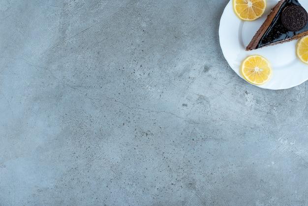 Tranche de gâteau au chocolat avec des tranches de citron sur une plaque blanche. photo de haute qualité