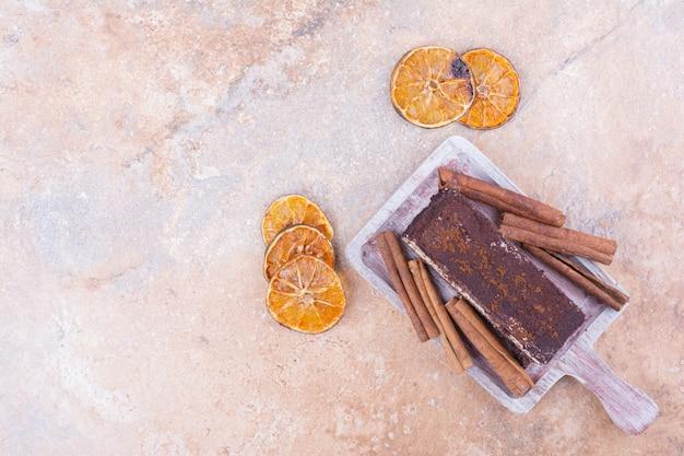 Une tranche de gâteau au chocolat avec des tranches d'orange et des cannelles