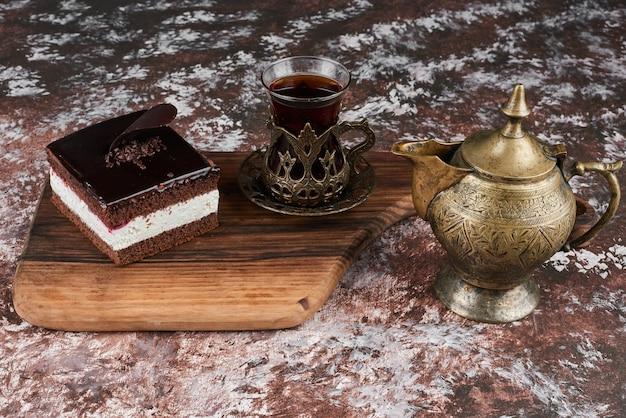 Une tranche de gâteau au fromage au chocolat avec un verre de thé.
