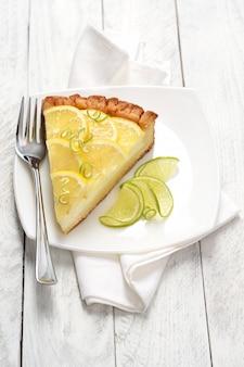 Tranche de gâteau au fromage aux agrumes sur plaque blanche