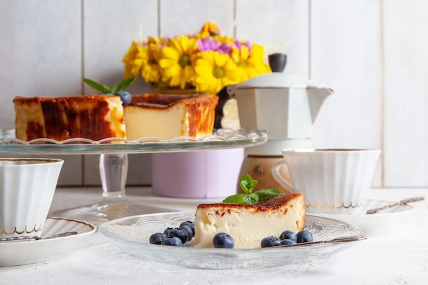 Tranche de gâteau au fromage brûlé basque maison sur une assiette avec des myrtilles et des feuilles de menthe sur une surface légère, tasses de café, cafetière geyser, bouquet de fleurs jaunes.