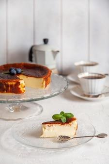 Tranche de gâteau au fromage brûlé basque maison sur une assiette avec des myrtilles et des feuilles de menthe sur une surface légère, des tasses de café et une cafetière geyser.