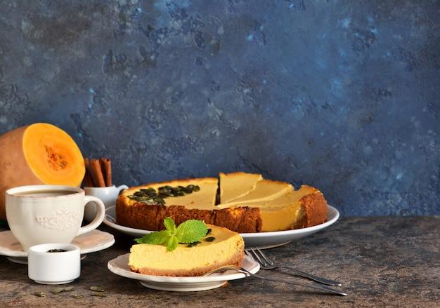 Tranche de gâteau au fromage à la citrouille avec une tasse de café sur un fond de béton.