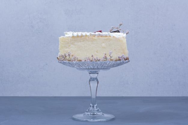 Une tranche de gâteau au fromage dans une soucoupe en verre sur fond bleu