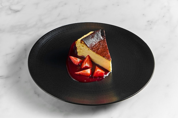 Tranche de gâteau au fromage, gâteau au fromage classique de style new york servi dans une assiette noire sur une surface en marbre