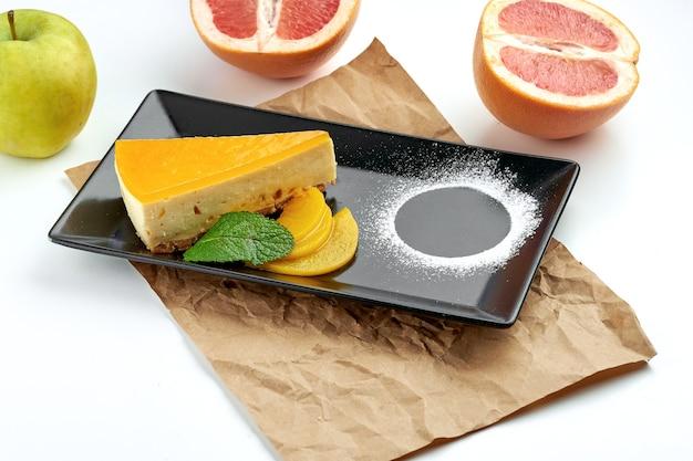Tranche de gâteau au fromage new york classique à la pêche, servi dans une assiette noire sur une surface blanche