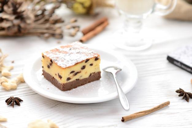 Tranche de gâteau au fromage new york ordinaire sur une plaque blanche sur fond en bois