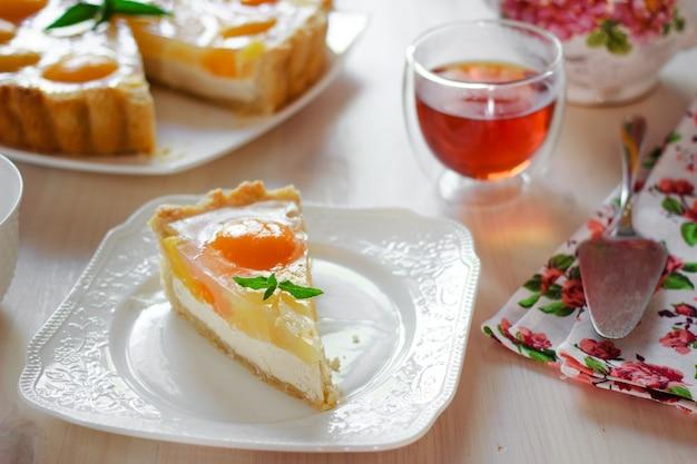 Une tranche de gâteau au fromage avec des pêches et de la gelée sur une table à l'heure du thé