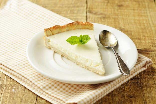 Tranche de gâteau au fromage simple sur une table en bois. dessert fait maison.