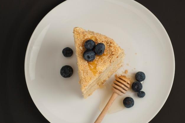 Tranche de gâteau au miel fait maison avec des myrtilles.
