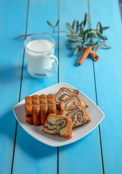 Une tranche de gâteau au miel traditionnel avec de la cannelle en poudre et une tasse de thé.