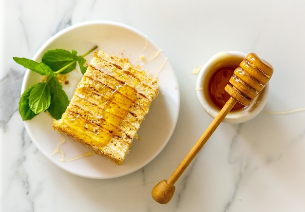 Tranche de gâteau au miel traditionnel russe fait maison sucré sur fond de pierre naturelle claire, vue de dessus décorée de menthe, de miel et de louche de miel en bois