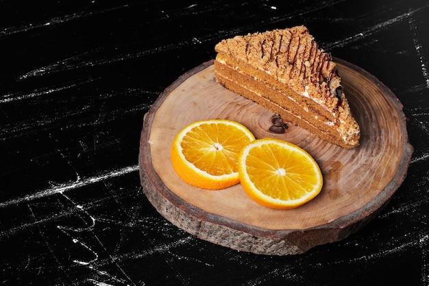 Une tranche de gâteau au miel avec des tranches d'orange.