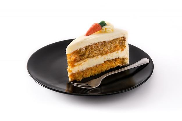 Tranche de gâteau aux carottes sucrées sur une assiette isolée on white
