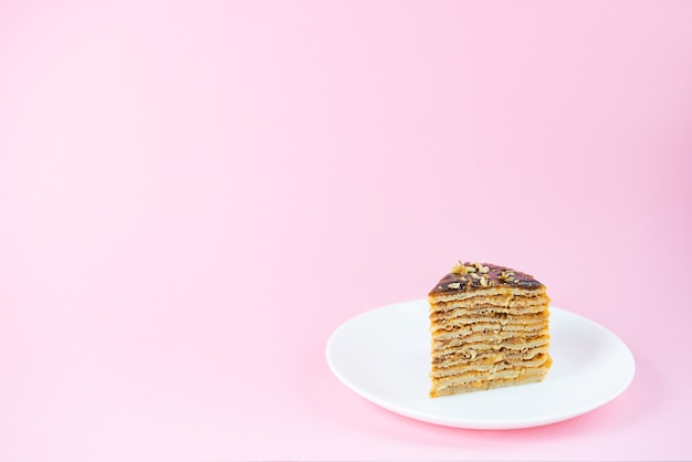 Une tranche de gâteau aux crêpes au caramel au chocolat et aux noix sur un mur rose