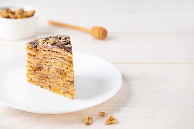 Une tranche de gâteau aux crêpes maison au caramel au chocolat et aux noix sur une table en bois
