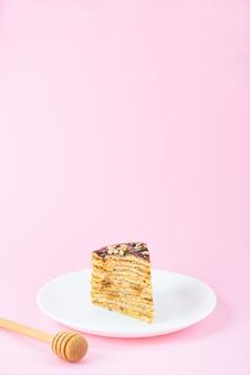 Une tranche de gâteau aux crêpes maison avec caramel au chocolat et noix sur un mur rose
