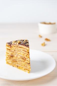 Une tranche de gâteau aux crêpes maison avec des noix de caramel au chocolat et du miel sur une table en bois