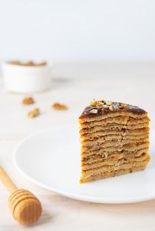 Une tranche de gâteau aux crêpes maison avec des noix de caramel au chocolat et framboises sur une plaque blanche