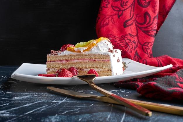 Une tranche de gâteau aux fruits dans une assiette blanche.