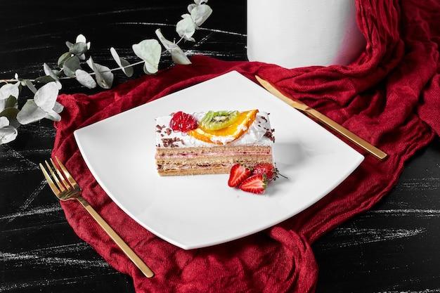 Tranche de gâteau aux fruits sur fond noir