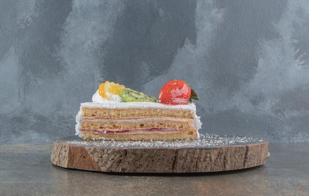 Tranche de gâteau aux fruits sur une planche de bois