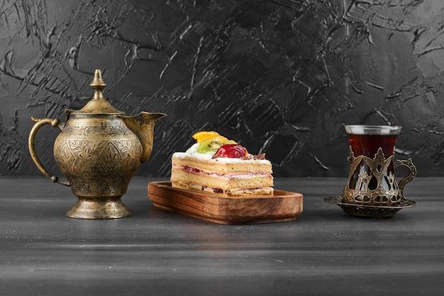 Une tranche de gâteau aux fruits avec un verre de thé.