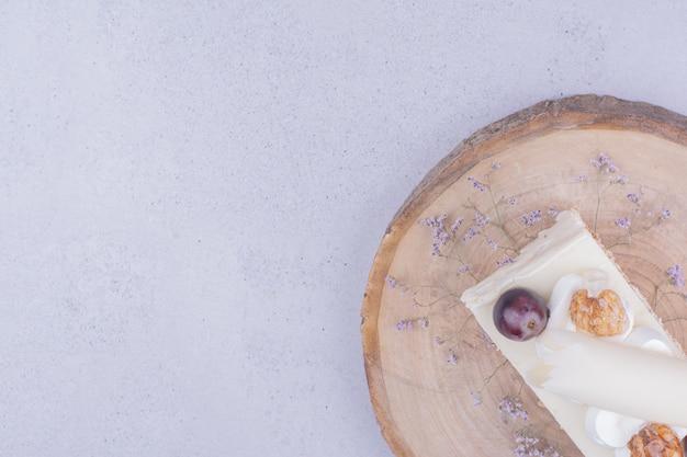 Une tranche de gâteau aux noix et raisins sur planche de bois.