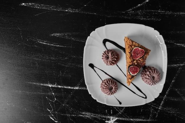 Une tranche de gâteau avec des biscuits au cacao dans une assiette blanche.