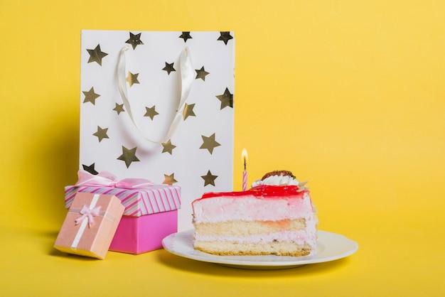 Tranche de gâteau avec une bougie illuminée; sac à provisions en forme d'étoile; et coffret sur fond jaune