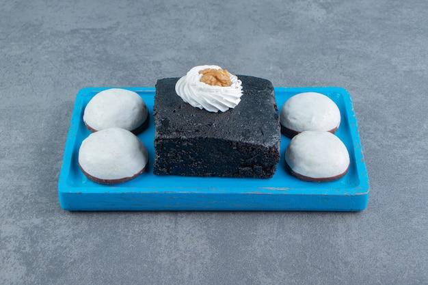Tranche de gâteau brownie et biscuits sur plaque bleue.