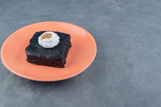 Tranche de gâteau brownie sur plaque orange.