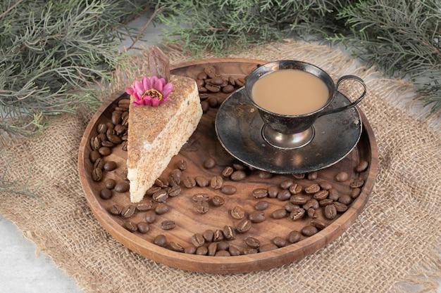 Tranche de gâteau, café et grains de café sur une plaque en bois